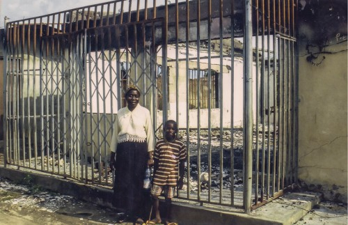 Mother and child outside their burnt home in Odi